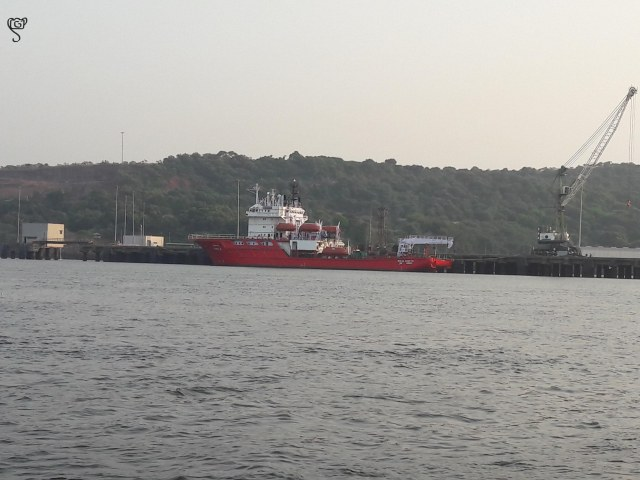 A bright red cargo ship at the Jetty in the backwaters