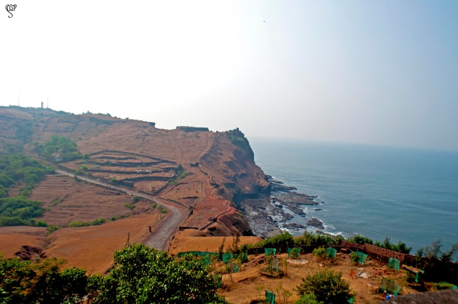 The view of the fort walls and the road and the tiny lighthouse on the other hill