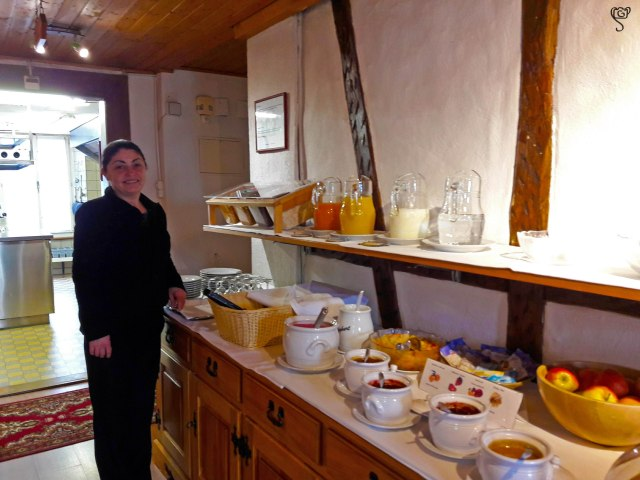 The smiling lady of our hotel with the breakfast spread