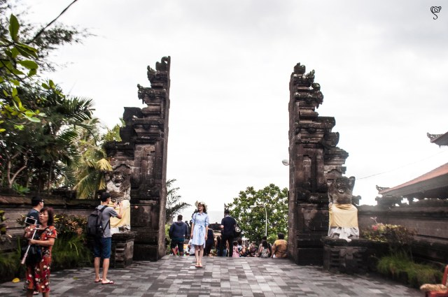 A woman posing for her friend in front of the split gate in Tanah Lot