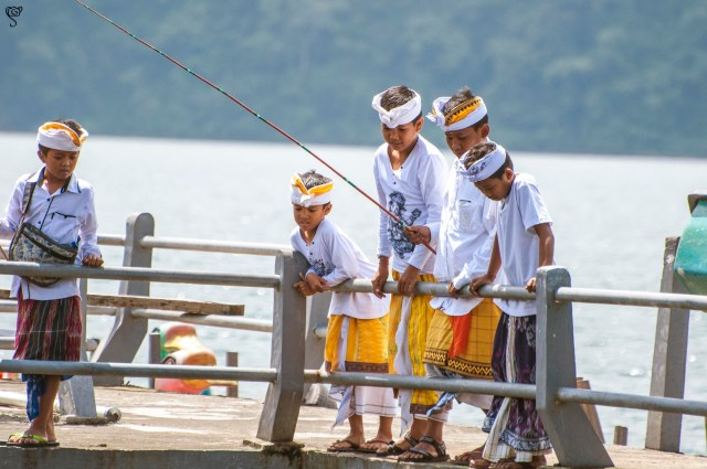 Kids in traditional attire busy in fishing