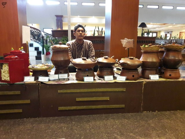 A Javanese man in traditional attire serving traditional food