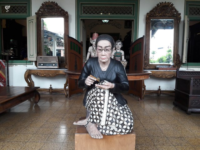 A lifelike sculpture of an aged lady doing Batik work