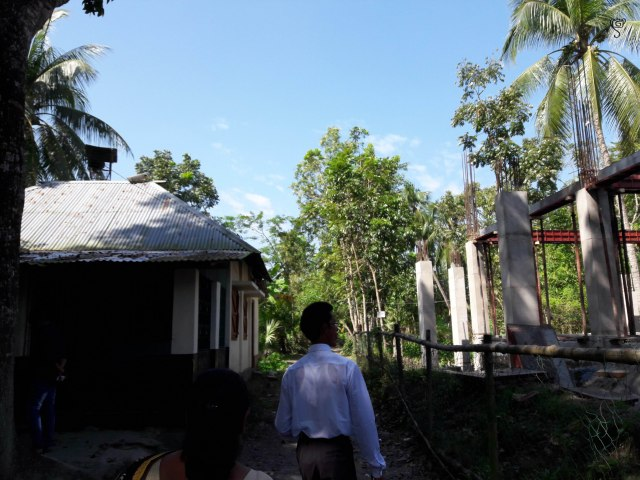 My newly found big brother guiding us to their house. The new school building is under construction on the right