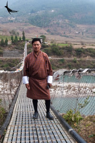 Lakey Drakpa posing on the suspension bridge in Punakha