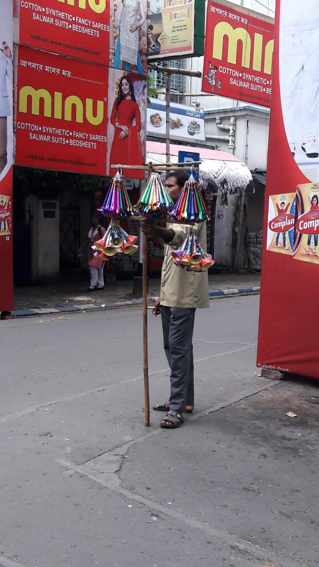 Street vendor standing in front of flex of big brands