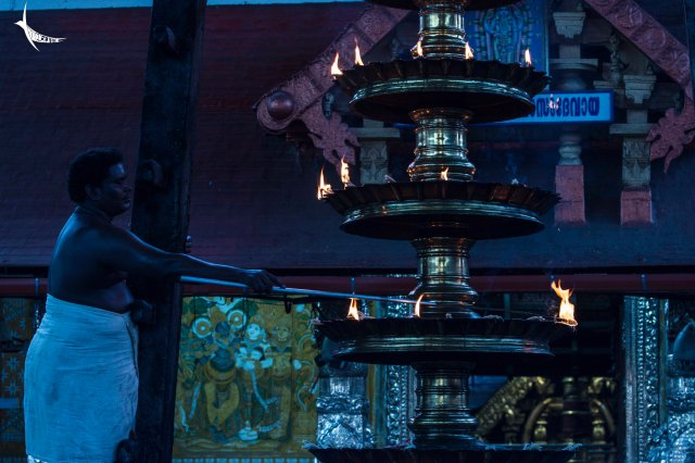 Man lighting the huge lamp in front of the main temple