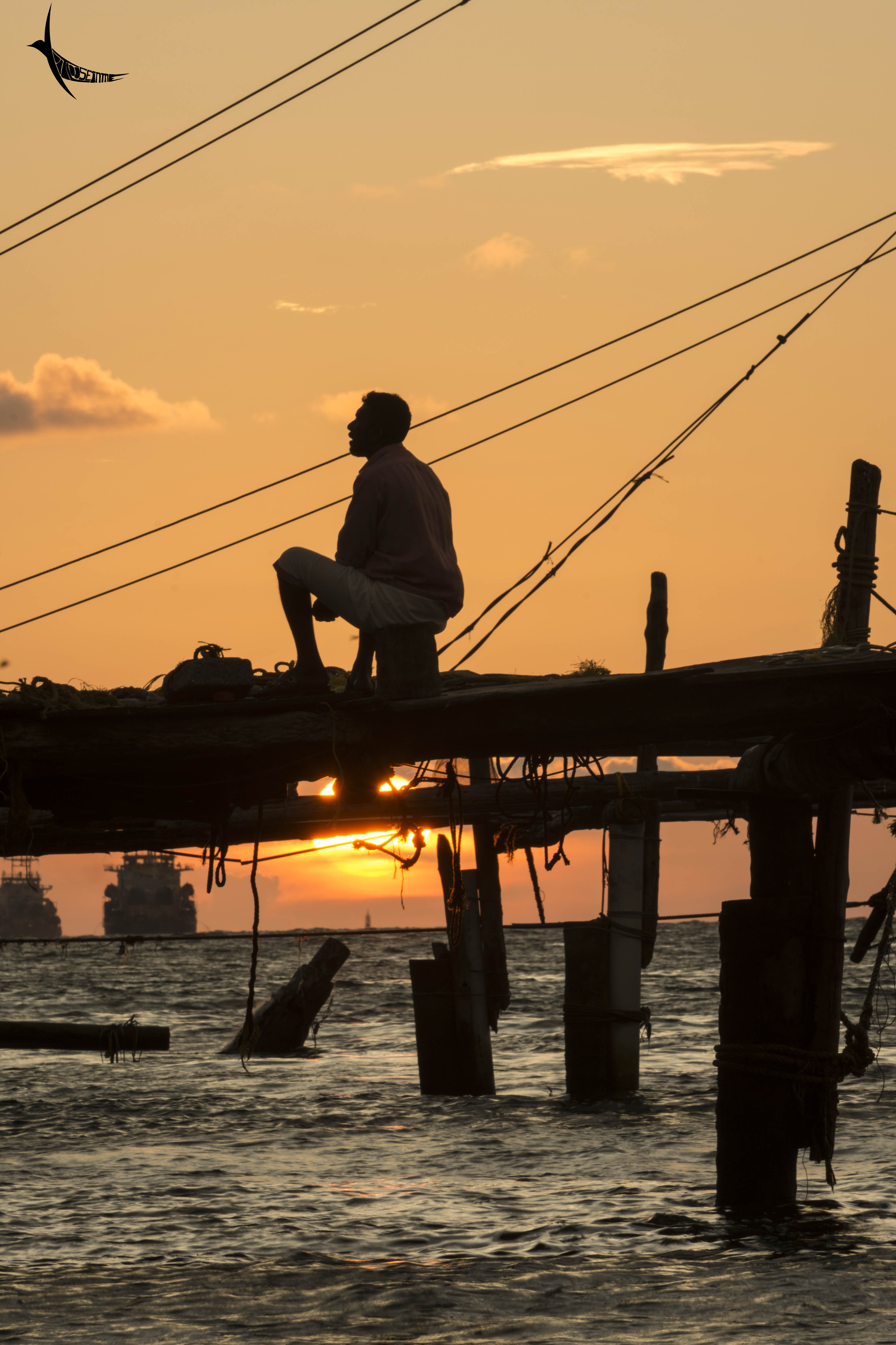 A fisherman rests on a pole after the laborious task