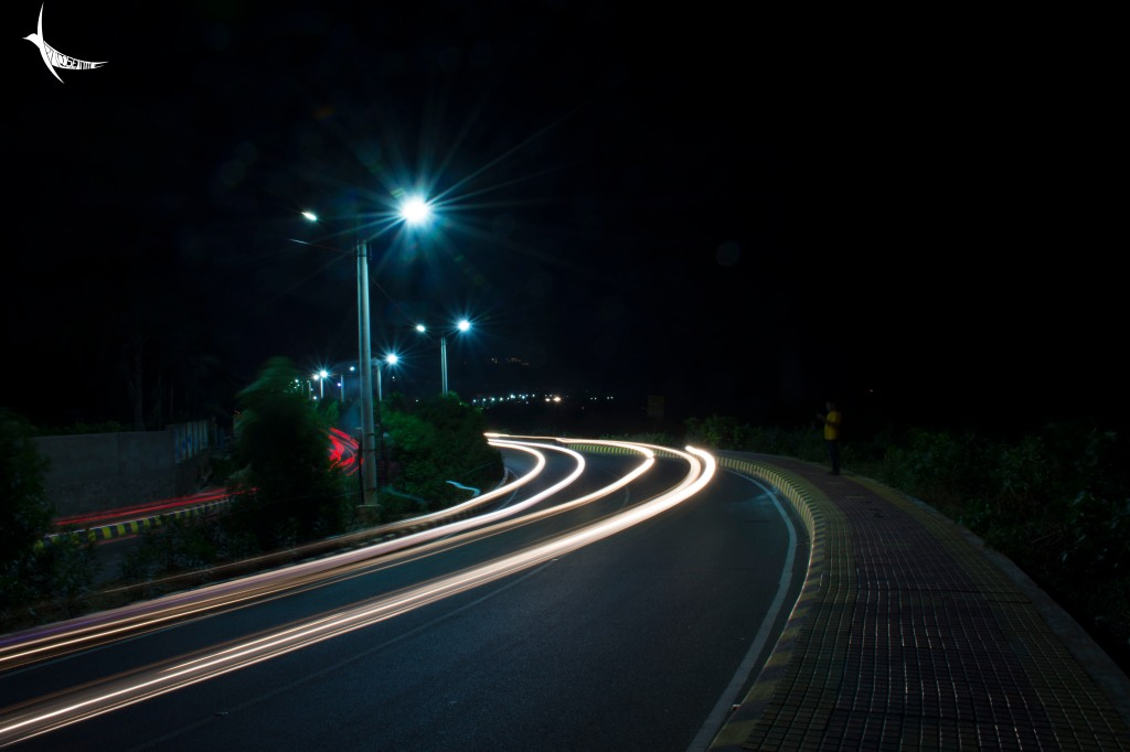 The street lights, headlights and taillights painting the road