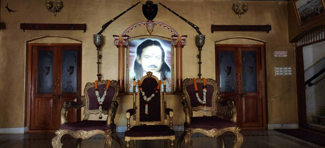 A hall in Bastar Palace showcasing the thrones and the portrait of the king