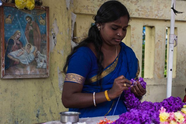 A lovely lady weaving a beautiful garland outside the Basilica